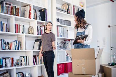 Bücherregale ausmisten, zwei Frauen mit Büchern und einer Kiste