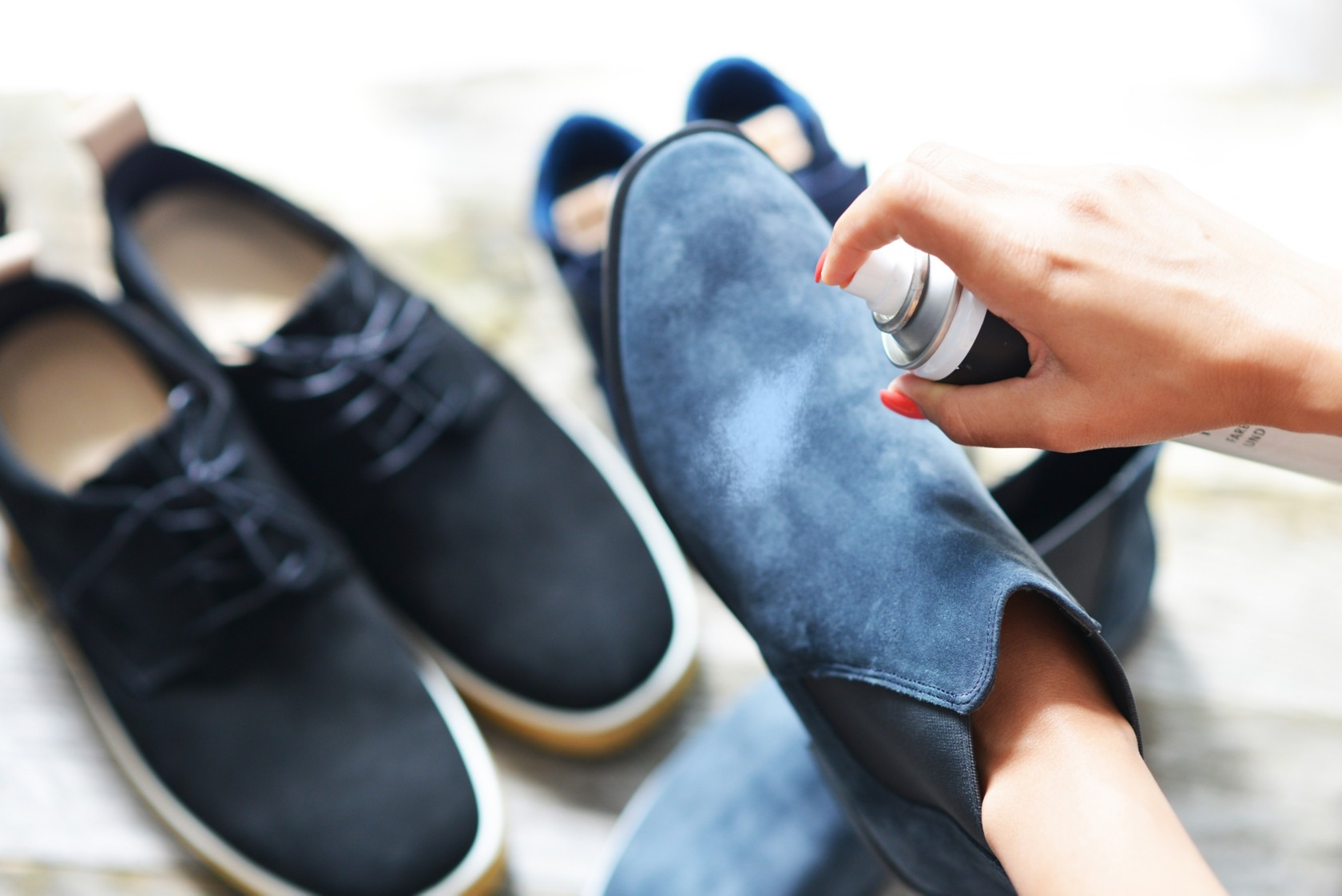 Helle Wildlederschuhe reinigen, Imprägnierspray wird auf ein ein paar blaue Schuhe gesprüht