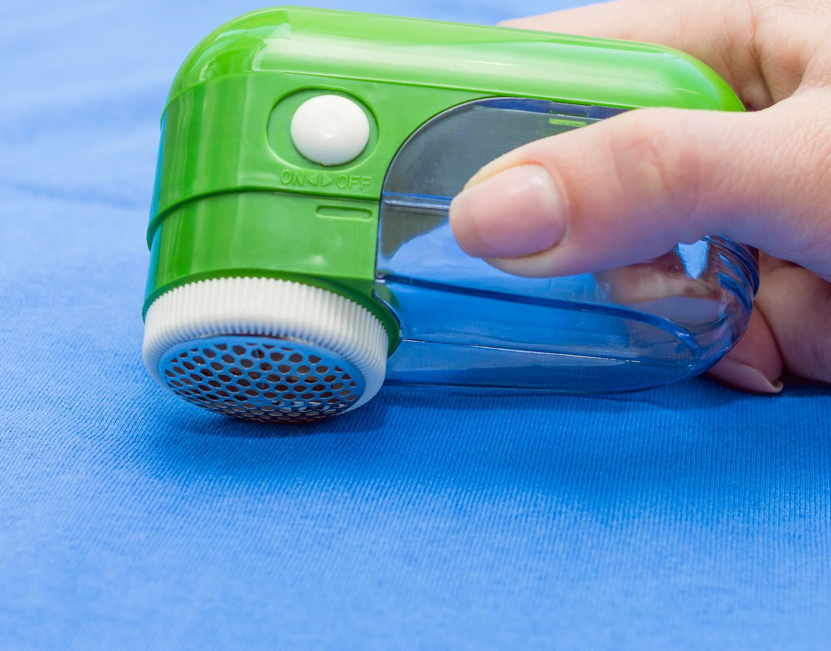 Hausmittel gegen Fusseln, Fusselrasierer auf blauem Stoff