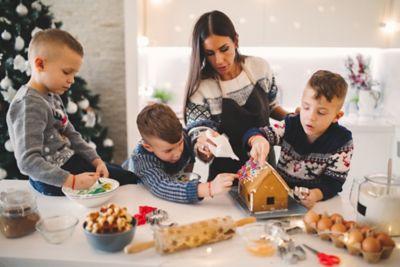 Lebkuchenhaus basteln, Frau mit drei Jungen verziert Lebkuchenhaus