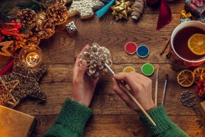 Weihnachtsdeko basteln, Frau mit Tannenzapfen und Pinsel
