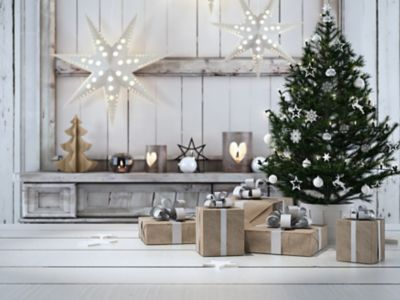 Tannenbaum schmücken, Weihnachtsbaum im Wohnzimmer, unter dem Baum liegen Geschenke