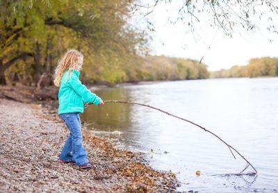 Fleece waschen, Mädchen mit hellblauer Fleecejacke spielt mit einem Zweig