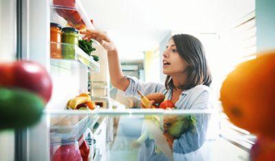 Obst richtig lagern, Frau räumt Kühlschrank ein