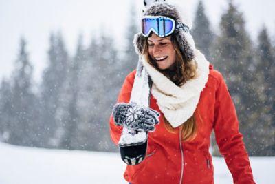 Skijacken waschen, Frau trägt Skis