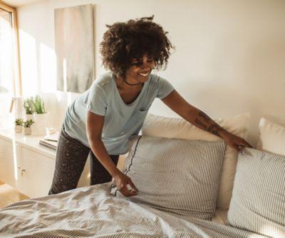 wiosenne porządki w sypialni: młoda kobieta ścieli łóżko