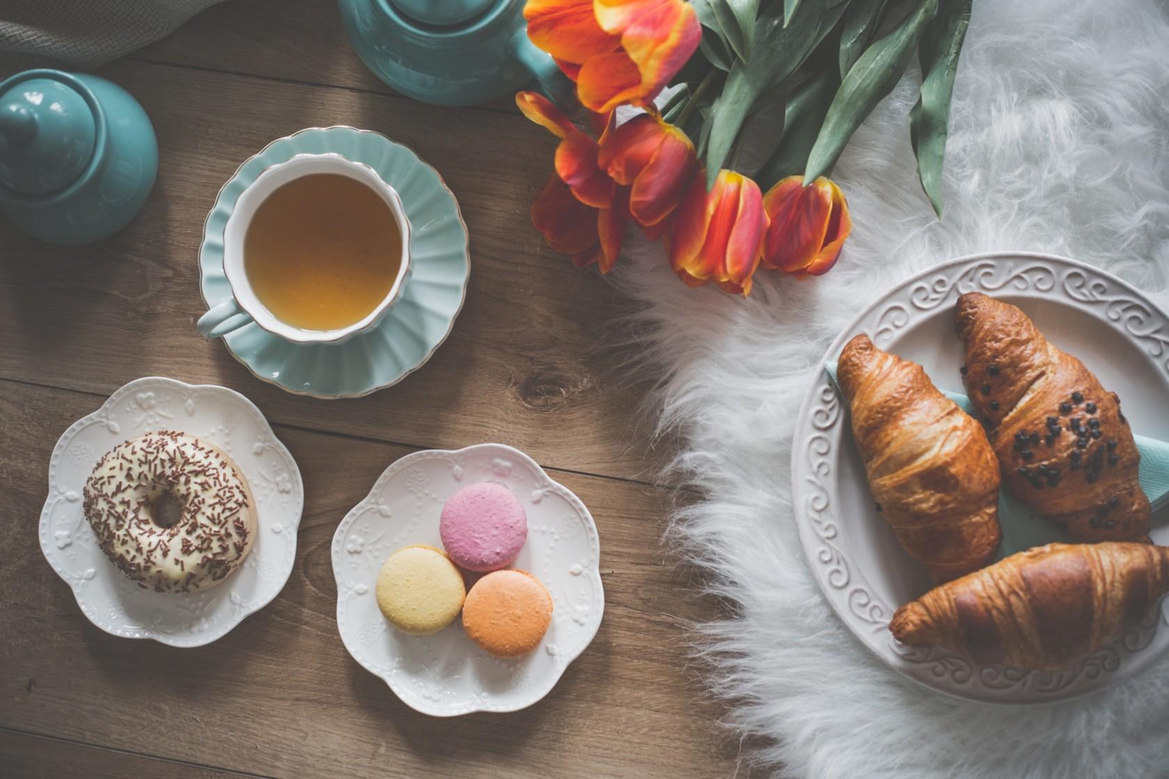 Kunstfell reinigen, weißes Kunstfell liegt auf dem Boden, Teller mit Croissants steht auf dem Kunstpelz