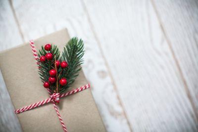Weihnachtsgeschenk mit Tannenzweig auf hellem Holzboden