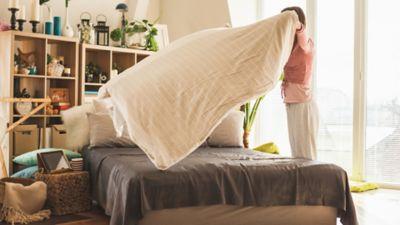 Bettwäsche Reinigung, Bettdecke wird aufgeschüttelt