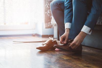 Anzugshosen waschen, ein Mann zieht seine Schuhe an und trägt eine Anzugshose