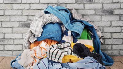Frühjahrsputz Kleiderschrank, Ein Stapel ungeordneter Kleidung liegt auf dem Holzboden.