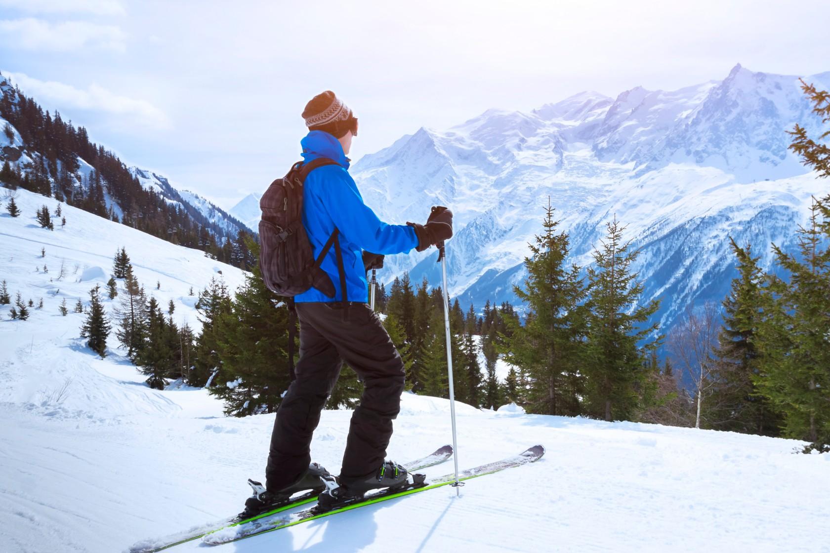 Skibekleidung, ein Mann mit blauer Skijacke steht auf seinen Skis