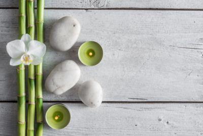 Arrangement aus Bambus, weißen Steinen und grünen Teelichtern