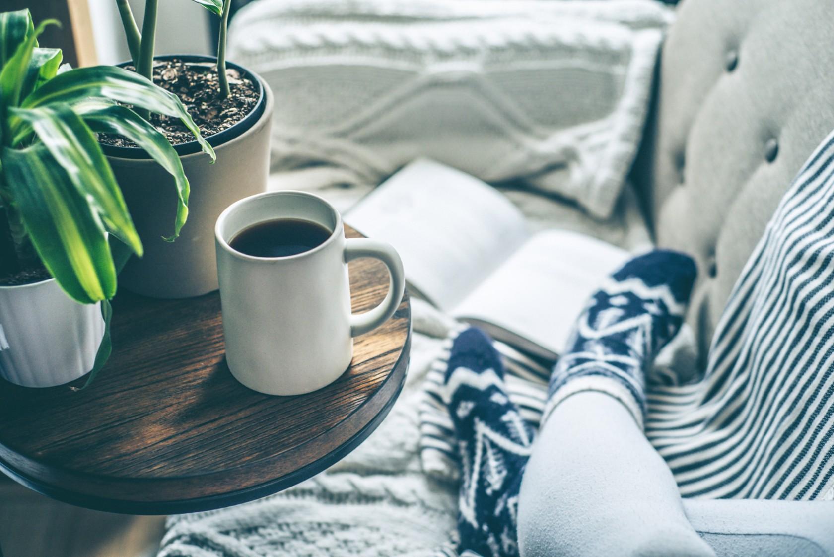 Ökologisch im Winter, Frau sitzt mit einer Decke und einer Tasse Kaffee auf dem Sofa