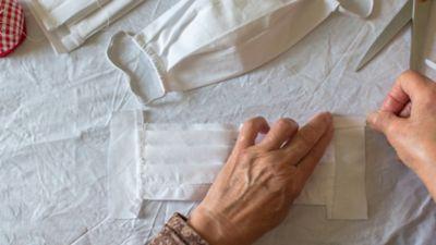 Mundschutz selber machen, ein Paar Hände näht einen Mundschutz aus Stoff