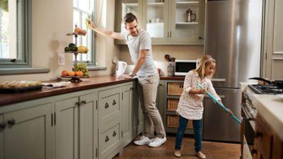 Küche putzen, Mutter mit Kind wischen die Kuchenablage