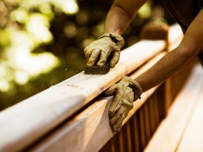 Outdoor-Möbel, Holzbank wird mit Sandpapier geschliffen.