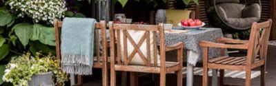 Meble ogrodowe, drewniany stół i krzesła na tarasie w zielonym ogrodzie.