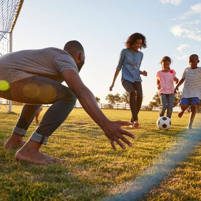 A young family is playing soccer