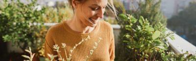 Outdoor Flecken und wie du sie wieder loswirst, Frau mit Pflanzen auf Terrasse