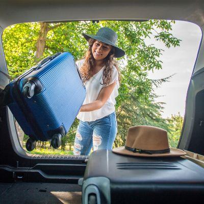 Packliste für eine perfekte Urlaubsvorbereitung, junge Frau lädt Koffer in ihr Auto