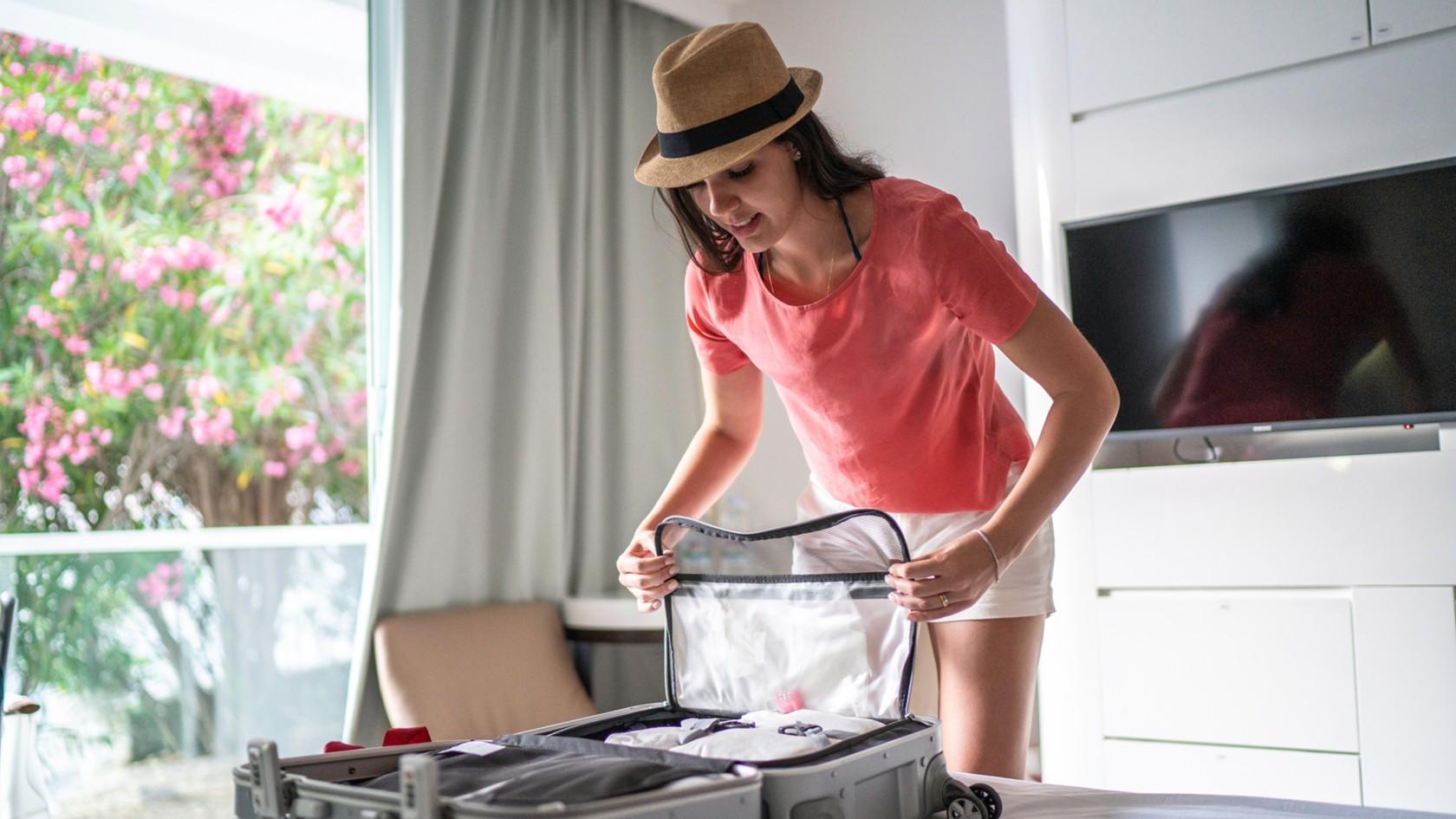 Packliste für eine perfekte Urlaubsvorbereitung, Frau mit Hut packt ihren Koffer