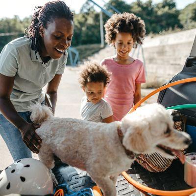 Sommerurlaub mit dem Auto, Familie packt Kofferraum ein