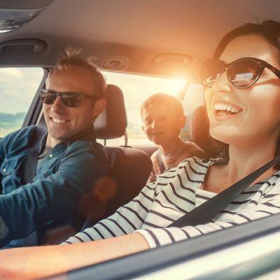 Familienurlaub am Strand, Vater, Mutter und Kind sitzen im Auto