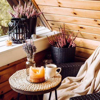 Genieße zu jeder Jahreszeit das Leben auf deinem Balkon. Ein gemütlicher Balkon mit Wolldecke und heißem Tee.