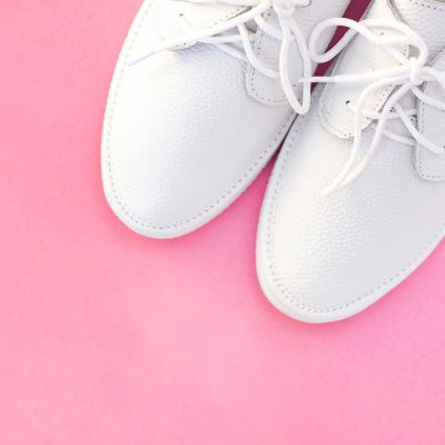 white leather shoes over a pink background