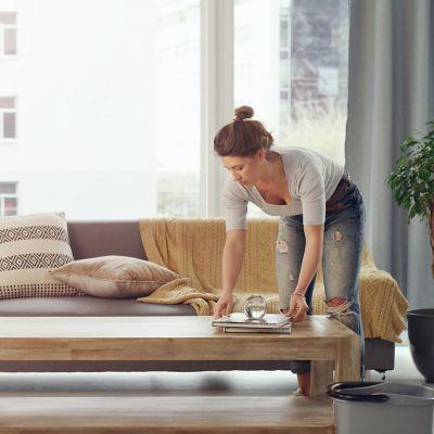 Ordnung schaffen, Frau räumt ihr Wohnzimmer auf