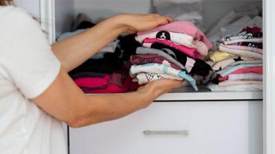 Kleidung ausmisten, T-Shirts werden aus dem Kleiderschrank gehalt