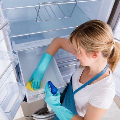 Kühlschrank reinigen, Frau putzt Kühlschrankfach