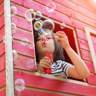 Seifenblasen selber machen, Kind im Baumhaus bläst Seifenblasen