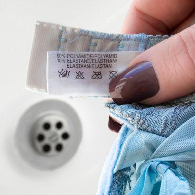kobieta sprawdzająca etykietę dotyczącą prania na ubraniu