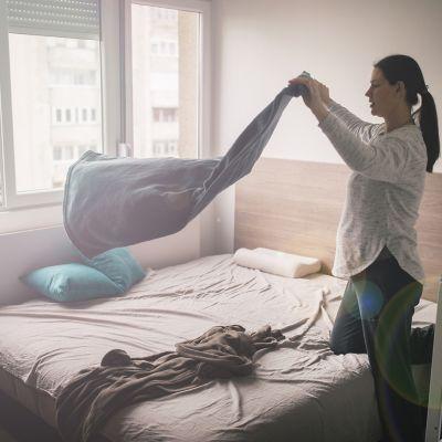 Bettwanzen bekämpfen, Frau schüttelt Bettzeug aus