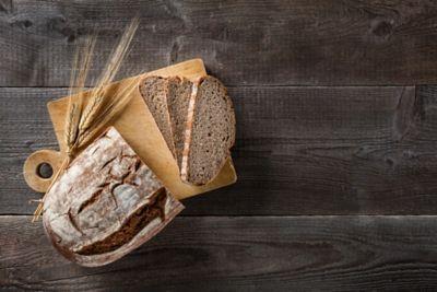Altes Brot verwerten, ein halber Laib Brot liegt neben zwei Brotscheiben auf einem Holzbrett
