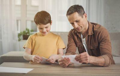 Vater bastelt mit Sohn Origami mit Toilettenpapier