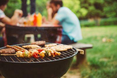 Fleisch und Schaschlikspieße mit Gemüse liegen auf schwarzem Kugelgrill