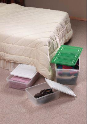 Einzelbett vor dem Plastikboxen zum Verstauen stehen, eine Kist ist halb unter dem Bett