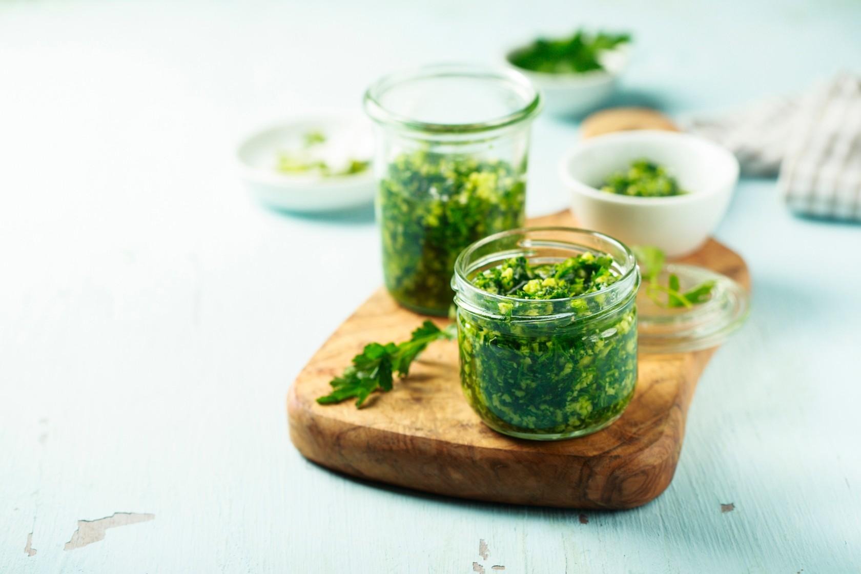 Pesto in Einmachgläsern stehen auf einem Brett aus Olivenholz auf dem ein Rucolablatt liegt.