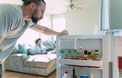Essensreste wiederverwenden in der der Küche, Mann blickt in Kühlschrank