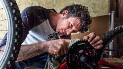 Kette reinigen, Mann reinigt Fahrradkette in seiner Garage