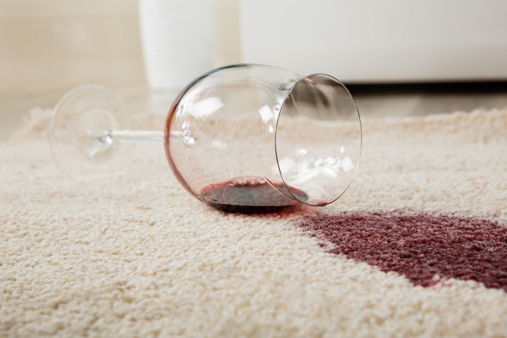 Teppichboden reinigen von einem Weinfleck, ein Glas Rotwein ist umgekippt