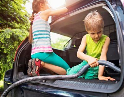 Zwei Kinder, ein Mädchen und ein Junge sitzen im Kofferraum eines Autos. Der Junge saugt und das Mädchen säubert die Gummidichtungen des Kofferraums