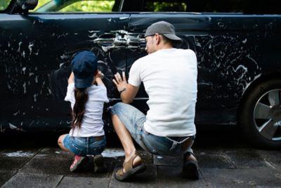 Vater schäumt mit Tochter gemeinsam das Auto ein