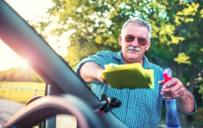 Ein älterer Mann reinigt die Frontscheibe eines Autos von Außen, mit Glasreiniger und Mikrofasertuch