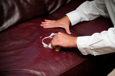 Couch reinigen, braune Ledercouch wird abgewischt