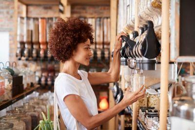 Einkaufen ohne Plastik, Frau füllt Glas