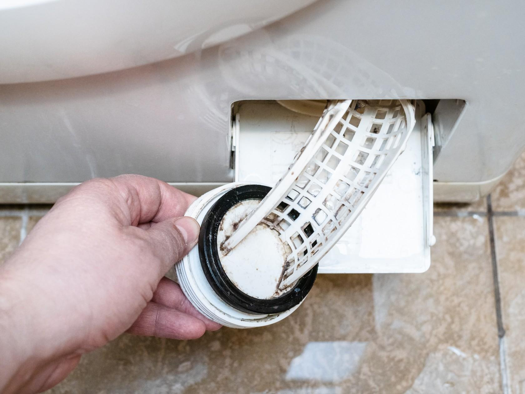 Waschmaschine Pumpe verstopft, Filter wird mit Hand herausgezogen